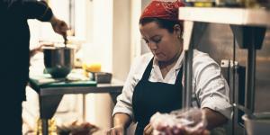 Hispanic woman wearing read bandana over hair in restaurant kitchen