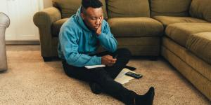young black entrepreneur stressing over financial documents on ground