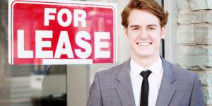 man in front of for lease sign