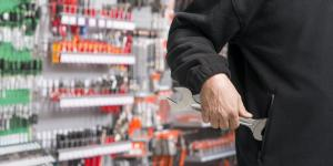 white man wearing a black sweatshirt putting a wrench in his pocket