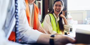 young asian woman laughing with coworker while wearing yellow reflective work vest