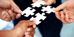 people holding puzzle pieces