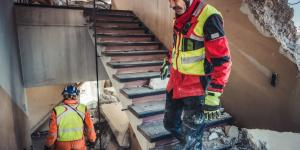 two men in safety gear examine the ruins of a building