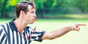 referee blowing penalty whistle