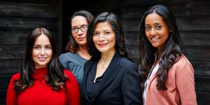 four hispanic business women standing together