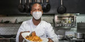 black restaurant owner in chefs coat and mask presenting a dish