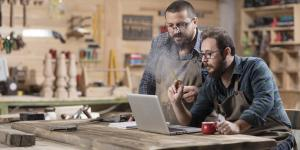 two men in woodworking studio discuss something in front of computer