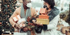black couple wearing masks and holding presents while christmas tree shopping