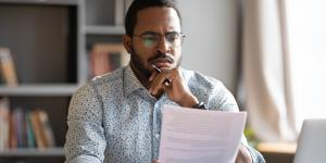 black business owner in button up shirt reading papers in his hand