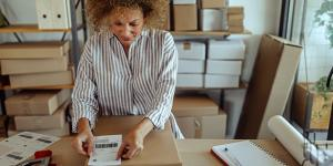 multi racial woman in white striped top puts shipping label on brown cardboard box