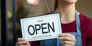 small business owner flips sign to open