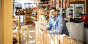 owner of specialty store standing behind counter in blue button up