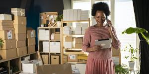 black business woman standing in at home office on tablet surrounded by boxes