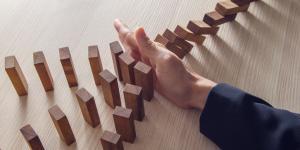 hand stops falling dominoes