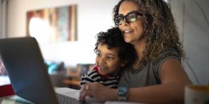 woman sitting at laptop with a child