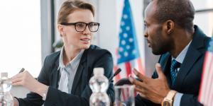 white woman and black man in suits talk with the american flag behind them