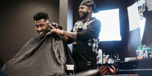black barber giving another black man a haircut