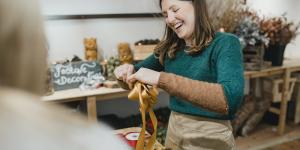 white woman in green sweater laughs while tying a ribbon