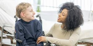 woman talking with boy in wheelchair