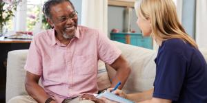 woman social worker talks to senior man