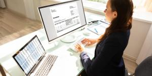 businesswoman types invoice on computer