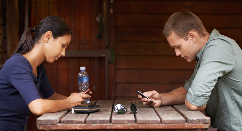 two people texting at a table