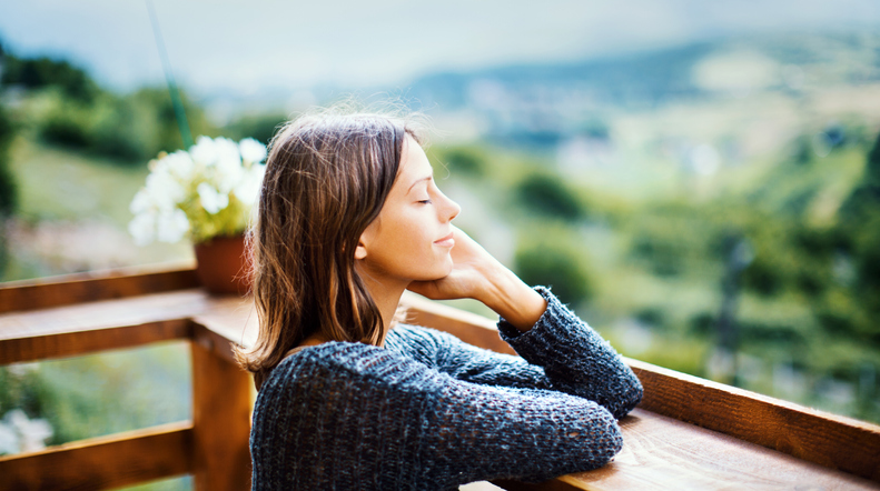 woman getting fresh air on balcony