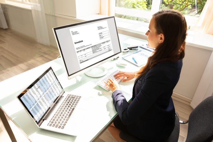 businesswoman types invoice on computer