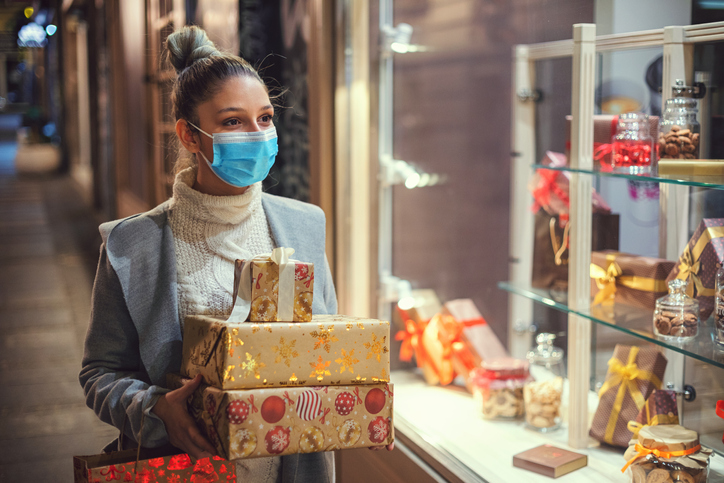 woman holds presents while walking down street wearing mask