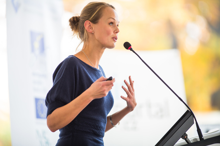 woman presenting at podium with a microphone