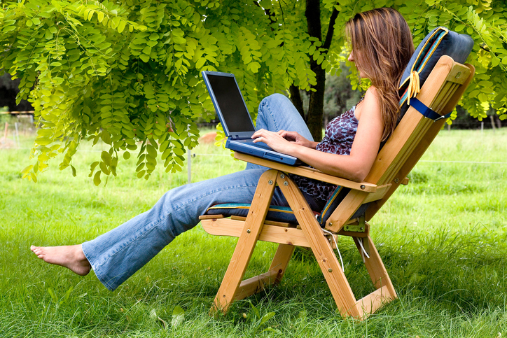 woman on laptop outside in deck chair