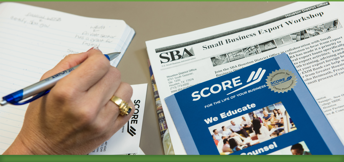 Person holding a pen with a SCORE Small Business Exporting Workshop packet