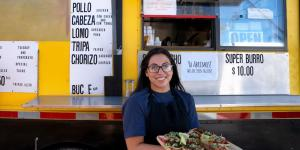 young hispanic woman standing in front of food truck with a tray of tacos