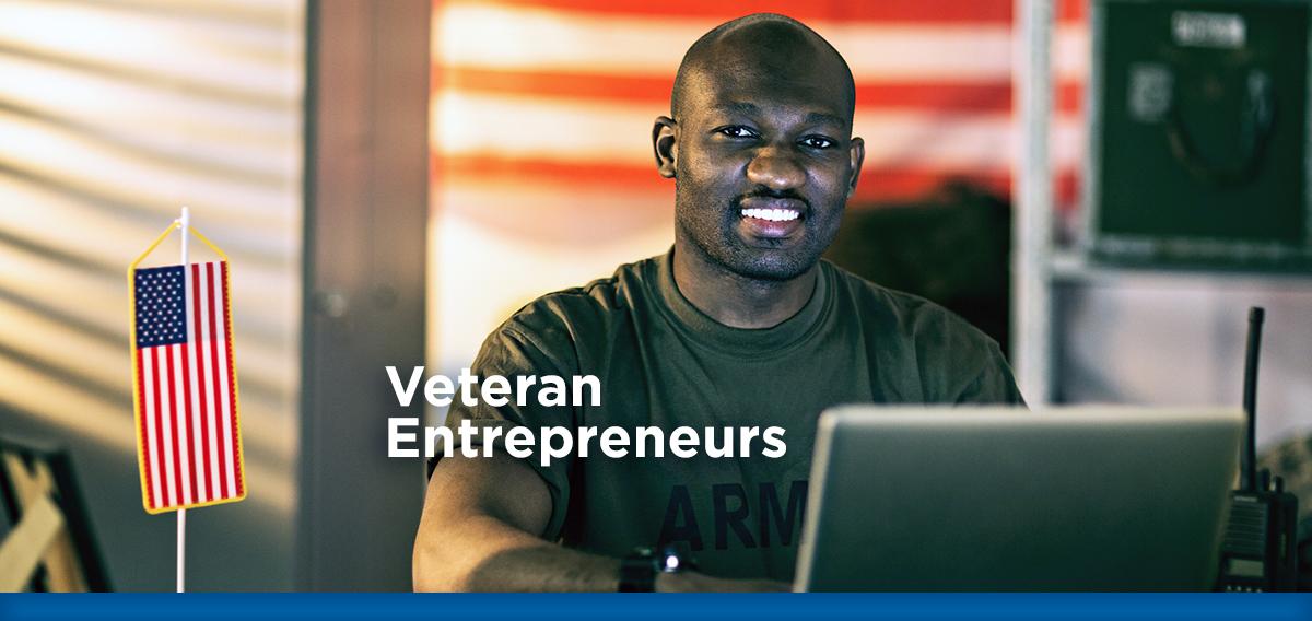 U.S. Army Veteran sitting at his desk smiling at camera