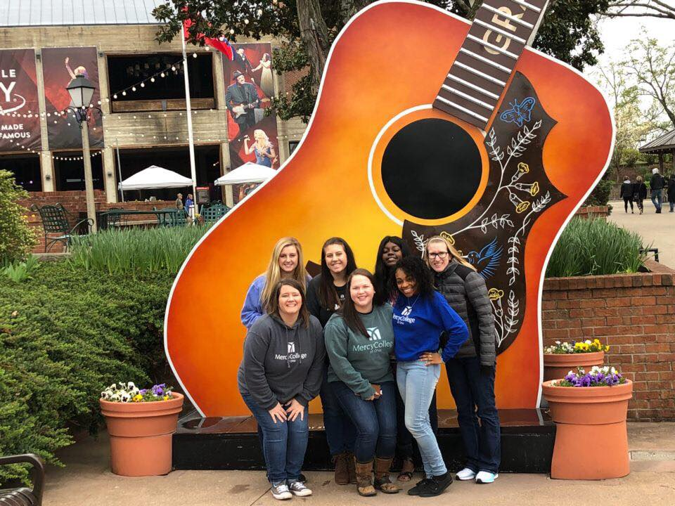 Image of Mercy College students (unidentified) in Nashville with large music city guitar