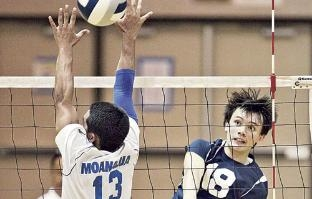 Kamehameha-Hawaii's Evan Enriques scored over Moanalua's Zarin Augustiro during the third set of their state semifinal volleyball match.