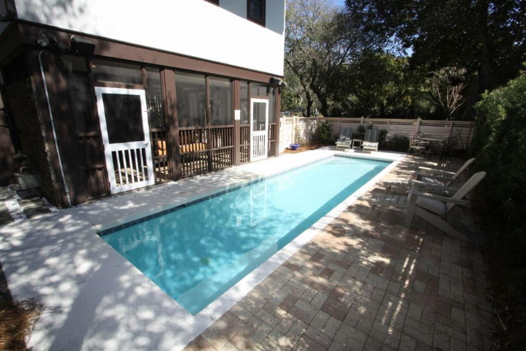 Large sunny pool towards porch area under home