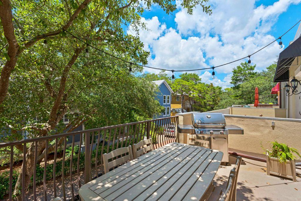 Outdoor dining table and gas grill off living area