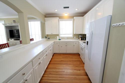 Kitchen has corian countertops and white appliance