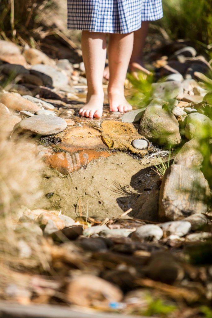 ELC Student walking barefoot in outdoor environment