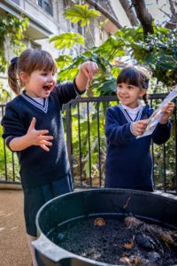 2 ELC Girls playing with worms in the garden