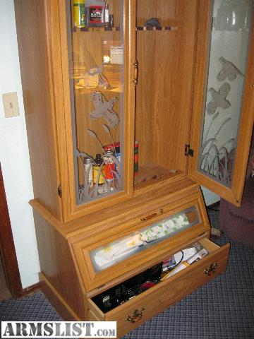 I HAVE FOR SALE A VERY NICE WOODEN (12) GUN CABINET. IT HAS 2 GLASS ETCHED  DOORS WITH LOCK AND KEYS, 1 DROP DOWN DRAWER THAT LOCKS, AND A PULL OUT  DRAWER.