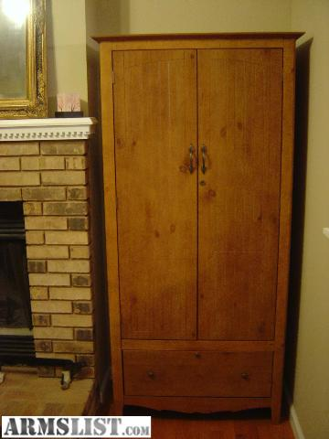 nice locking wood gun cabinet with padded slots for scoped on the left and lower profile guns on the right