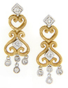 .32 carats total weight of diamonds are set in these heart shaped 14K two-tone gold earrings