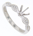 This 14K white gold antique style engagement ring mounting highlights diamonds set in the hand-chased, marquis-shaped shoulders