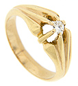 A single diamond is set on the top of this 14K yellow gold retro-modern ring