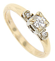 A single diamond is set on each shoulder of this 14K yellow gold antique engagement ring
