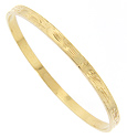 Engraved designs cover the surface of this 14K yellow gold vintage bangle bracelet