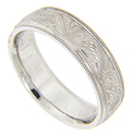 Milgrain edges flank an elaborate engraved design on this 14K white gold antique style men's wedding band