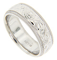 An ornate engraved floral motif covers this 14K white gold antique style mens wedding band